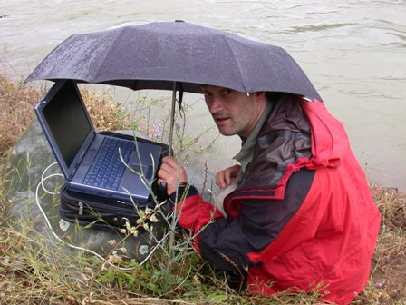 staff member under umbrella with laptop